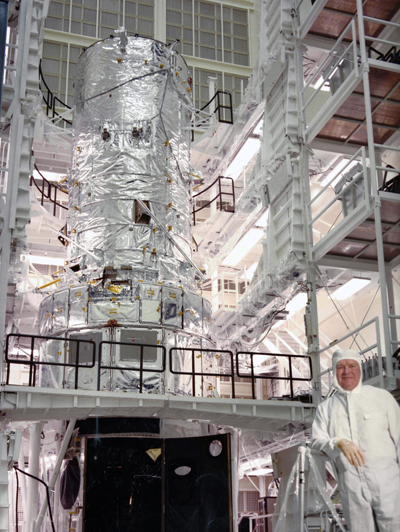 Max Hunter poses in the clean room as Hubble awaits deployment.